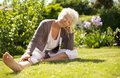 Mature woman sitting down on grass comfortably in garden looking at you outdoors Stock Photography