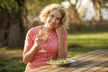A mature woman sitting at a garden bench eating a meal Royalty Free Stock Photo