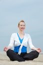 Mature woman sitting in yoga position at beach portrait of a happy Stock Image