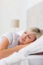 Mature woman sleeping with eyes closed in bed pretty the Stock Image