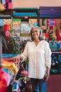 Mature woman smiling while working in her textiles shop Royalty Free Stock Photo