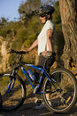 Mature woman standing beside bicycle on mountain trail, looking at scenery, smiling, side view Royalty Free Stock Photo