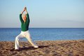 Mature woman stretching on the beach senior practicing yoga during morning Stock Photos