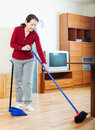 Mature woman sweeping the floor at home Royalty Free Stock Images