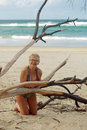 Mature woman travelling full body beach portrait of natural attractive senior happy in swimsuit by some drift wood at the beach Stock Photos