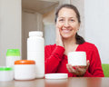 Mature woman uses cosmetic cream smiling in home interior Stock Photos
