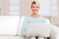 Mature woman using laptop happy at home Stock Images