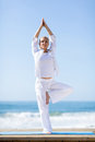 Mature woman yoga fit doing exercise outdoors on beach Royalty Free Stock Photos