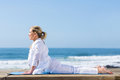 Mature woman yoga upward dog position on beach Royalty Free Stock Image