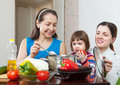 Mature women and her adult daughter with baby girl cook veggie lunch in kitchen Royalty Free Stock Photos