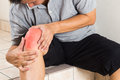 Matured man suffering painful knee joint seated on steps acute pain staircase Stock Photo