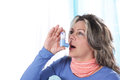 Matured woman inhales asthma spray Royalty Free Stock Photo