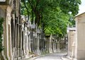 Mausoleums aged and weathered lining both sides of a path in pere lachaise cemetery paris france Stock Images