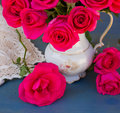 Mauve blooming roses close up bouquet on a blue table Royalty Free Stock Image