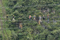 Tourists walking a suspended cable bridge in Ecuador