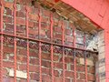 Bricked-Over Window in an Abandoned Building with Red Ironwork Scrolled Bars Royalty Free Stock Photo