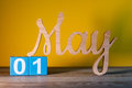 May 1st. Day 1 of month, wooden carved calendar on yellow background. Spring time concept Royalty Free Stock Photo