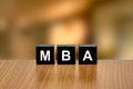 Mba or master of business administration on black block with blurred background Royalty Free Stock Photography