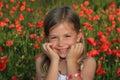 Mädchen, das auf einem Mohnblumegebiet lacht Stockbilder