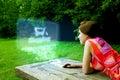 Mädchen, das online im Park kauft Lizenzfreies Stockfoto