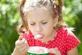 Mädchen in einer roten Bluse mit Geschmack Eiscreme essend Lizenzfreie Stockbilder