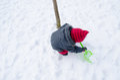 Mädchen mit rotem hutschaufel grabungsschnee Stockfoto
