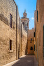 Mdina scene tiny street in with limestone buildings and a church Stock Photos