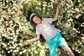 Meadow flowers on a boy in blue shorts and a cap is in daisies Stock Photos