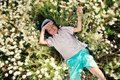 Meadow flowers on a boy in blue shorts and a cap is in daisies Stock Image