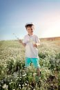 Meadow flowers boy in blue shorts and a cap walks on chamomile field Stock Photo