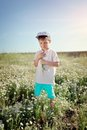 Meadow flowers boy in blue shorts and a cap walks on chamomile field Stock Photography