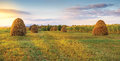 Meadow and haystack on a sunset Royalty Free Stock Image