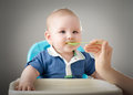 Meal time cute baby boy eating with blonde hair blue eyes and a dirty face isolated on gray background the infant is having Stock Photos