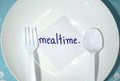 Mealtime white empty plastic plate and cutlery with card remind for Stock Image