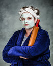 Mean and ugly housewife with facial mask hair rollers rolling pin Stock Images
