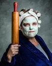 Mean and ugly housewife with facial mask hair rollers rolling pin Stock Image