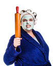 Mean and ugly housewife with facial mask hair rollers rolling pin isolated on white Royalty Free Stock Photography