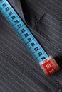 Measure tape being stretched on top of a classic coat striped gray suit Stock Photos