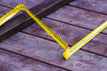 Measure thrice yellow tape on a wooden floor and cut once Stock Image
