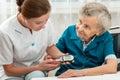 Measuring blood glucose level female nurse of senior woman Stock Photography