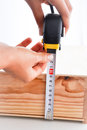 Measuring a box with roulette wooden an yellow Stock Photos