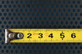 Measuring tape on a background with perforation of round holes metallic Royalty Free Stock Image