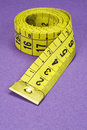 Measuring tape coiled yellow on purple background photo Stock Photography