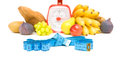 Measuring tape, kitchen scale and vegetables on a white backgrou Royalty Free Stock Photo