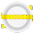 Measuring tape and plate as a conceptual diet icon Royalty Free Stock Photo