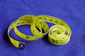 Measuring tape of the tailor on purple fabric Royalty Free Stock Photo