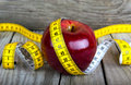 Measuring tape wrapped around a apple weight loss Royalty Free Stock Photo