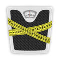 Measuring tape wrapped around bathroom scales concept of weight loss diet healthy lifestyle Royalty Free Stock Image