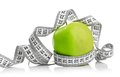 Measuring tape wrapped around a green apple as symbol of diet Stock Photos