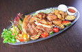 Meat allsorts with vegetables in oval metal plate on table Royalty Free Stock Photography